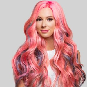 Young woman with Glam Seamless long hair extensions in bright candy pink and purple tones.
